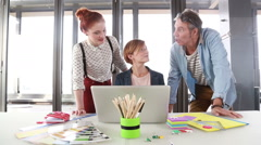Female creative executive showing to director and colleague project on laptop - stock footage