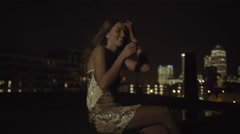 Young adult woman drinking on rooftop at party at night Stock Footage