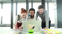 Male creative executive discussing new ideas on laptop with colleagues - stock footage