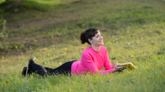 Woman reading book lying in the meadow Stock Footage