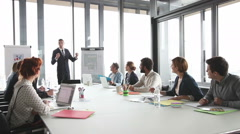 Young director giving presentation to colleagues in conference room - stock footage