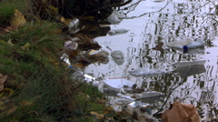Trash littered along pond bank Stock Footage