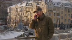 Man is Talking by a Mobile Phone on a Bridge Vintage Brown-Blocked Building is - stock footage