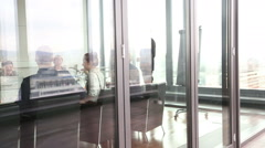 Colleagues on a meeting in conference room, behind glass wall Stock Footage