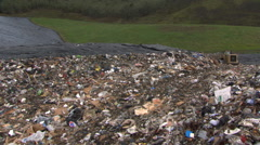 Left pan across compacted garbage in landfill Stock Footage