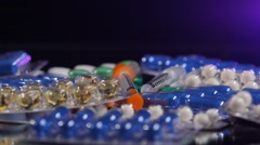 Some different contraceptive pills and two syringes, rotation, reflection, on Stock Footage