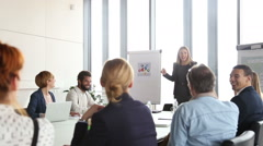 Beautiful smiling businesswoman giving presentation to colleagues - stock footage