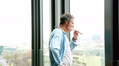 Profile of creative director standing by window, smoking electronic cigarette - stock footage