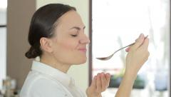 Young smiling woman testing the food in the kitchen, close up HD - stock footage