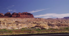 RV on highway in front of a painted landscape of mesas Stock Footage