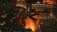 Close flight over casinos from Harrah's to the Palazzo in Las Vegas at night. - stock footage