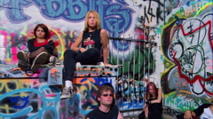 "Sullen-looking teens dressed in ""goth"" style sitting by a graffiti-covered wall - stock footage"