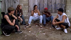 Young man rolling a joint and offering it to teenagers seated by him in an alley - stock footage