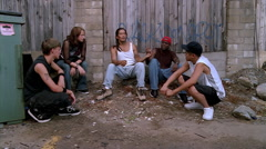 Teenagers passing a joint, encouraged by a young man sitting with them in an Stock Footage