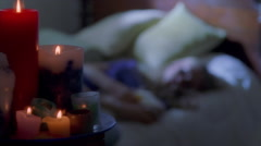 Rack focus from burning candles to teenage girl on a bed with a pill bottle in Stock Footage