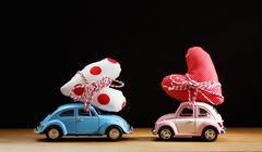 Miniature pink and blue cars carrying hearts - stock photo