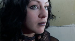 Three-quarter profile close-up of young woman with black lipstick and nose stud Stock Footage