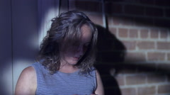 Young woman standing in shadows and wringing her hands Stock Footage