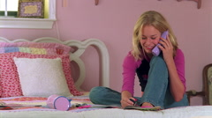 Teenage girl sitting in pink bedroom and painting her toenails while talking on Stock Footage