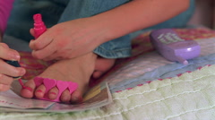 Close-up of teenage toes being polished pink - stock footage