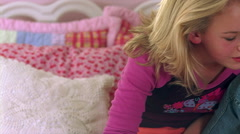 Close-up of blond teenager sitting on bed and looking toward her toes Stock Footage