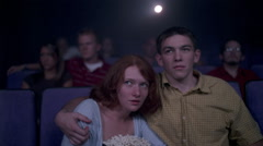 Young couple watching scary film in a  movie theater Stock Footage