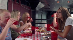 Teenagers sitting at long table in a pizza parlor Stock Footage