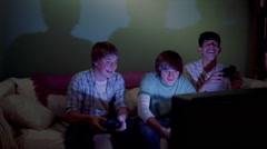 Three teenage boys playing an exciting video game in a living room Stock Footage