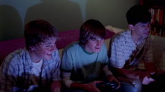 Three teenage boys reacting to moves in an exciting home video game Stock Footage