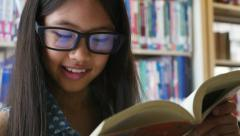 4K : Little Asian students reading a book in library Arkistovideo