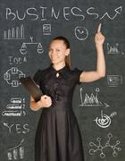 Business woman holding a clip board and points to the chalk-drawn graphics Stock Photos