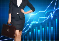 Business woman standing with a briefcase on background economic graphics - stock photo