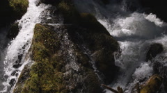 A mossy boulder splitting the stream of a waterfall Stock Footage