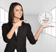 Office girl standing on background of light interior and holding clock with the Stock Photos