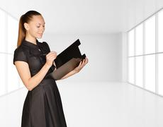 Office girl standing on background of light interior and is holding clipboard - stock photo