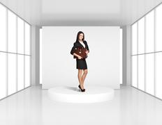 Woman with leather briefcase standing on the podium in bright room - stock photo