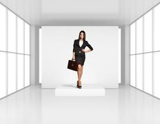 Young girl with leather briefcase standing on the podium in bright room - stock photo
