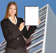 Business woman standing on background building, and indicates ballpoint pen in Stock Photos