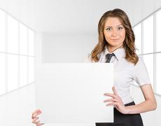 Office girl standing on background of light interior and is holding blank paper Stock Photos