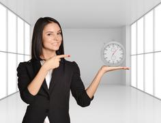 Office girl standing on background of light interior and holding stopwatch - stock photo