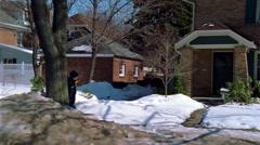 Little boy playfully throwing a snowball toward camera on a neighborhood - stock footage
