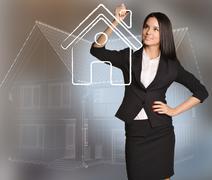 Woman draws house icon standing on background scheme cottage Stock Photos