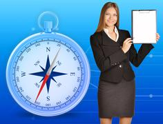 Office girl holding clipboard standing on blue background with compass Stock Photos