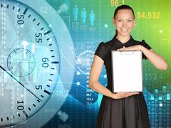 Young girl in a dress stands on background stopwatch holding clipboard - stock photo