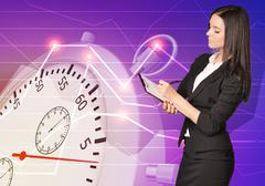 Young girl in office clothes writes data to the clipboard with stopwatch Stock Photos