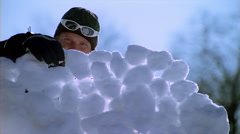 Man and woman building a snowball fort - stock footage