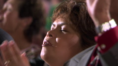 Close-up of woman's face as she sings among other members of a congregation - stock footage