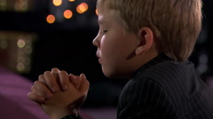 Close-up face of young boy praying with bowed head and folded hands Stock Footage