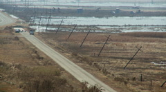 Elevated view of leaning power poles and flooded low-lying area by a rural road Stock Footage