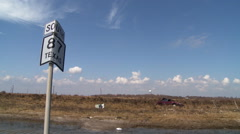 Wind-bent highway sign and wrecked car at roadside in aftermath of a hurricane Stock Footage